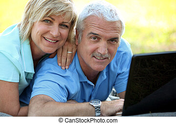 portrait of smiling mature couple with laptop outdoors