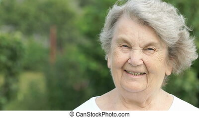 Portrait of smiling mature elderly woman outdoors - Portrait...