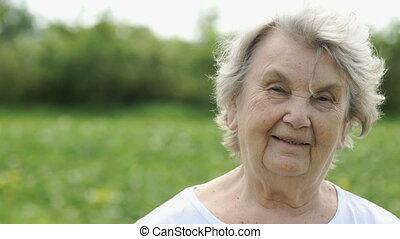 Portrait of smiling mature elderly woman outdoors