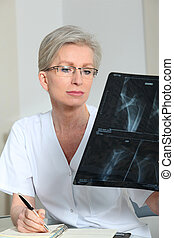 Portrait of smiling mature nurse in office looking at xray