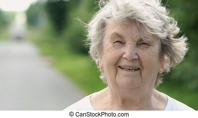 Portrait of smiling mature old woman outdoors in the background of road. Slow Motion