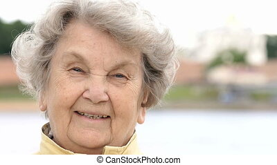 Portrait of smiling mature old woman outdoors