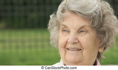 Portrait of smiling mature old woman outdoors - Portrait of...