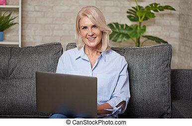 Portrait of smiling mature woman with laptop computer
