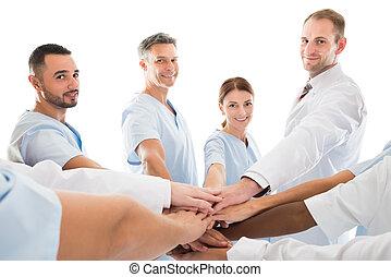 Portrait Of Smiling Medical Team Piling Hands - Portrait of...
