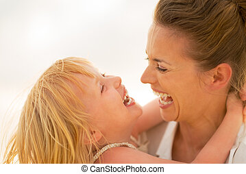 Portrait of smiling mother and baby girl hugging on the...