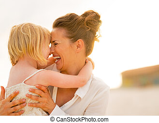 Portrait of smiling mother and baby girl hugging on the beach in