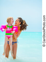 Portrait of smiling mother and baby girl in sea
