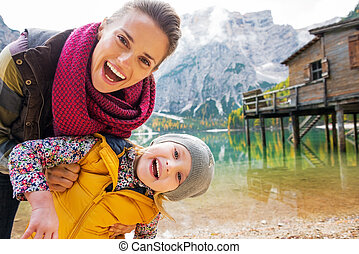 Portrait of smiling mother and baby on lake braies in south...