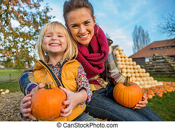 Portrait of smiling mother and child sitting on haystack with pu