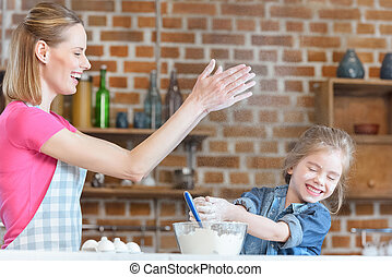 portrait of smiling mother and daughter having fun while cooking