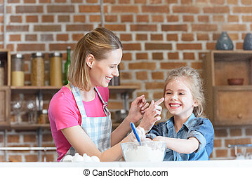 portrait of smiling mother and daughter having fun while cooking at home