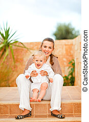 Portrait of smiling mother and happy baby sitting on staircase