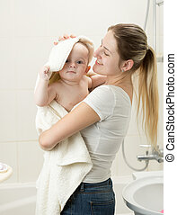 Portrait of smiling mother wiping her baby with towel after having bath
