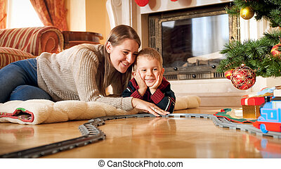 Portrait of smiling mother with her little son lying on wooden floor under Christmas tree and playing with toy railroad. Child receiving presents and toys on New Year or Xmas