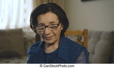 Portrait of smiling old woman puts on glasses and looks at camera