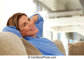 smiling older woman sitting on sofa at home