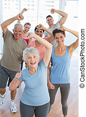Portrait of smiling people doing power fitness exercise at...
