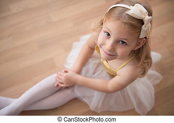 Portrait of smiling pretty diligent ballet girl sitting in ...