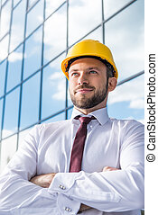 portrait of smiling professional architect in hard hat against building