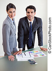 Portrait of smiling sales persons studying their results in...