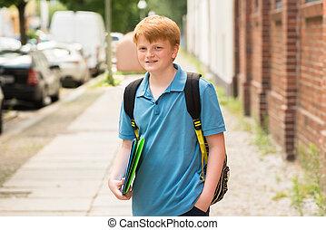 Smiling Schoolboy Standing On Sidewalk