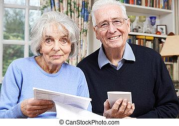 Portrait Of Smiling Senior Couple Reviewing Home Finances