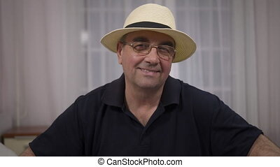 portrait of smiling senior man in hat