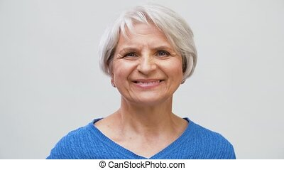 portrait of smiling senior woman touching her hair - old age...