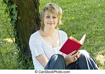 Portrait of smiling student reading book in nature