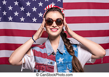 portrait of smiling stylish woman in sunglasses with american flag behind