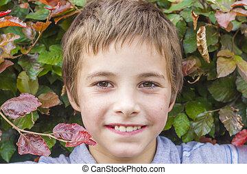 Portrait of smiling teenage boy at bush