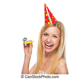 Portrait of smiling teenage girl in cap party horn blower