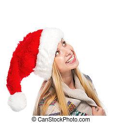 Portrait of smiling teenage girl in santa hat looking on copy space