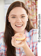 Portrait Of Smiling Teenage Girl On Eating Donut