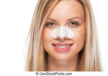 Portrait of smiling teenage girl with clear-up strips on...