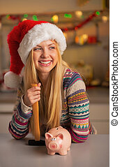 Portrait of smiling teenager girl in santa hat with piggy...