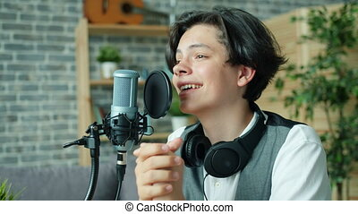 Portrait of smiling teenager speaking in mic in sound...