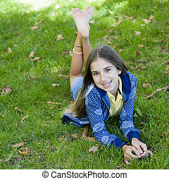 Portrait of Smiling Tween Girl lying On Grass Smiling To...