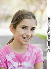 Portrait of Smiling Tween Girl with Braces Wearing Tye-dyed...