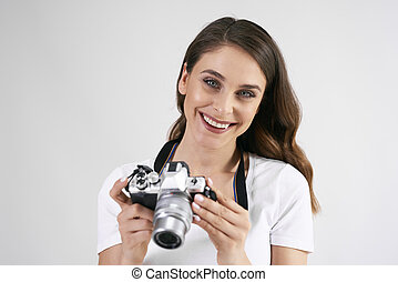Portrait of smiling woman holding a camera