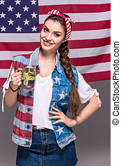 portrait of smiling woman holding drink in hand with american flag behind
