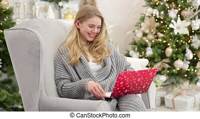Portrait of smiling young woman holding laptop on her laps and working. Sitting on comfortable armchair near christmas tree