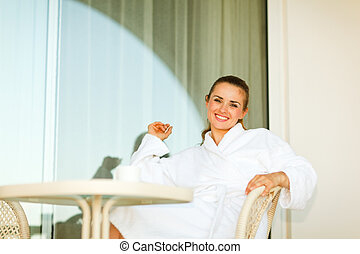 Portrait of smiling woman in bathrobe sitting at table on terrace