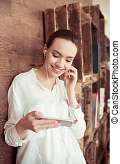 portrait of smiling woman in earphones using smartphone