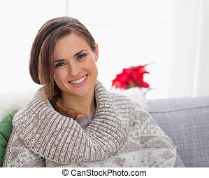 Portrait of smiling woman in knit sweater sitting on couch