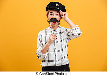 Portrait of smiling woman in plaid shirt and police cap holding paper moustache at her face, isolated over yellow background