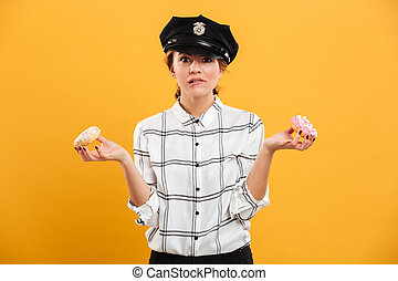 Portrait of smiling woman in plaid shirt and police cap posing on camera with donuts in hands, isolated over yellow background
