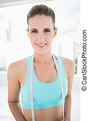 Portrait of smiling woman in sportswear holding measuring tape