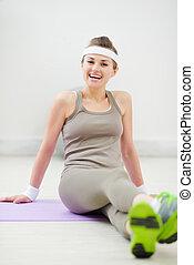 Portrait of smiling woman in sportswear sitting on floor